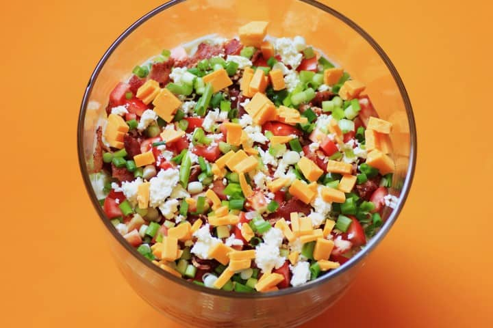 California Layered Salad in a clear glass salad bowl