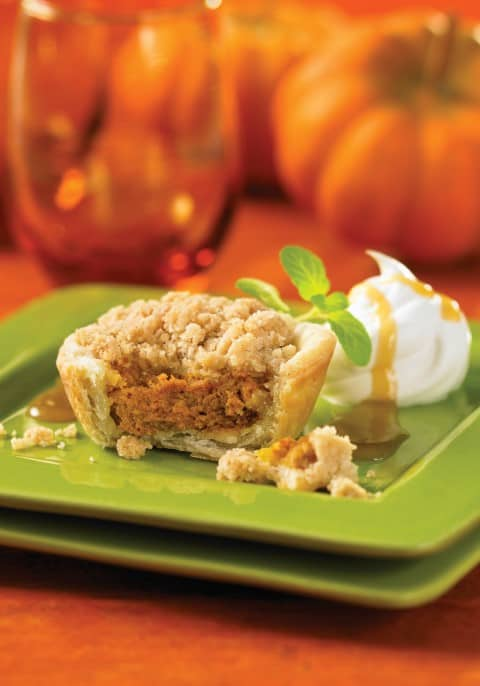 Pumpkin Pies with Spiced Walnut Streusel on a green plate with a bite missing