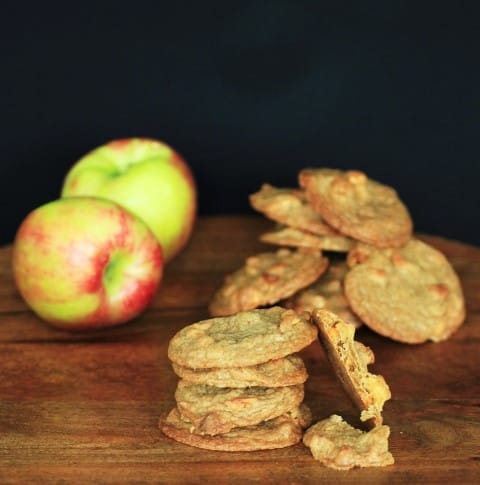 Apple Butterscotch Cookies stacked on a wooden board with whole apples