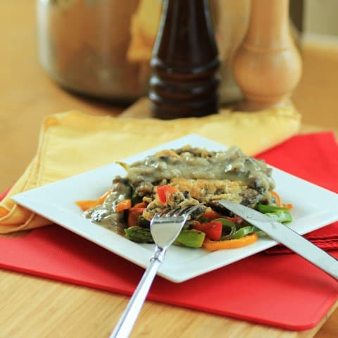 Chicken Fried Portobello Mushrooms on top of cook peppers with shallot gravy and a knife and fork