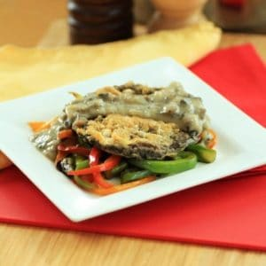 Chicken Fried Portobello Mushroom over vegetables on a square white plate