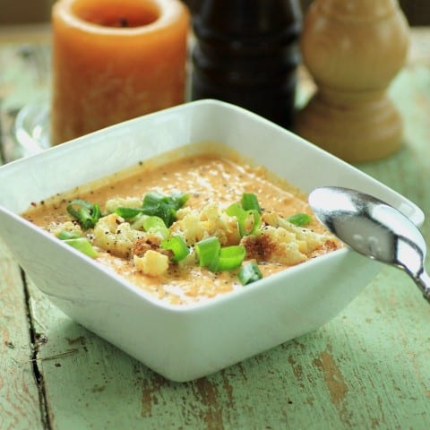 Curried Cauliflower Soup in a square white bowl with a spoon on a green wooden board