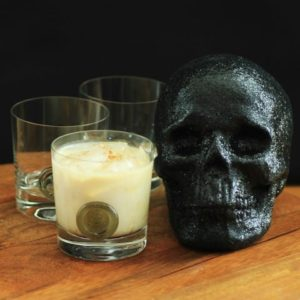 Heads Will Roll Cocktail in an old fashion glass sitting beside a black skull