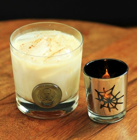 Heads Will Roll Cocktail in a cocktail glass with a spider votive candle on a wooden board