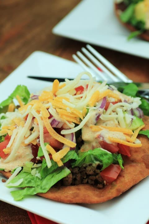 Udi's Gluten Free Tostados on a white plate topped with shredded cheese