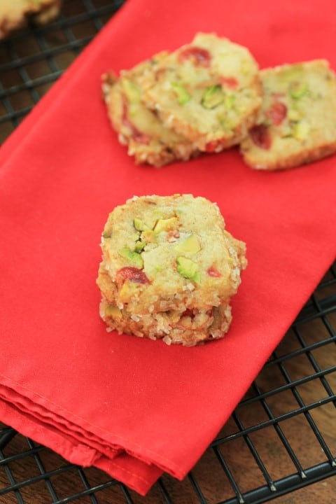 Cherry Pistachio Ice Box Cookies on a red napkin on a cooking rack.