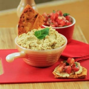 Mediterranean Hummus in a small white serving bowl with some on a cracker with tomotoes