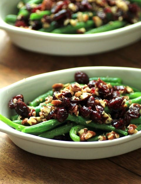 Green Beans with Pecans and Cranberries in a white oval serving dish