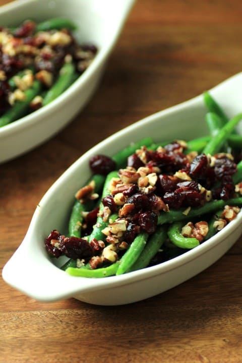 Green Beans with Pecans and Cranberries in a white oval serving dish on a wooden board