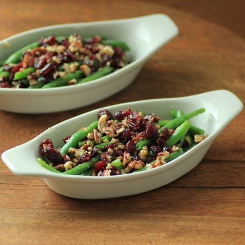 2 white serving dishes with Green Beans with Pecans and Cranberries in them