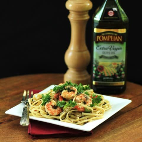 Shrimp and Linguini Olio on a square white plate with a fork and the bottle of olive oil in the background