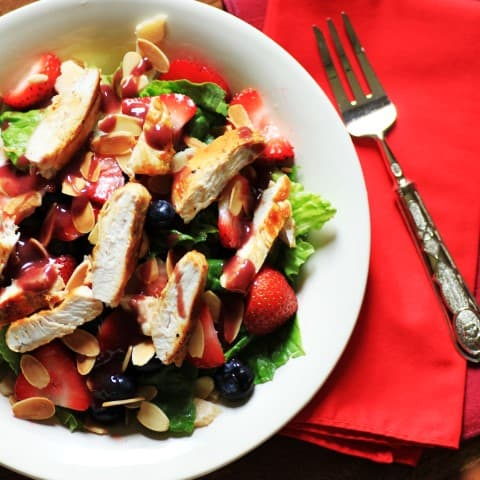 Wendy's Copycat Berry Almond Chicken Salad in a white bowl with a fork on a red napkin