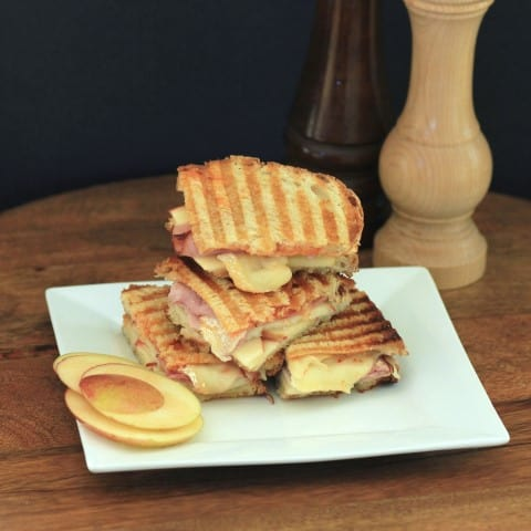 Apple, Brie and Ham Panini stacked up on a small white plate with apple slices on the side