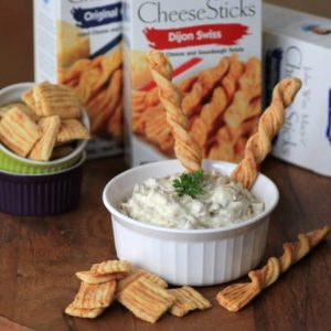 Caramelized Onion and Bacon Dip in a small white bowl with bread sticks for dipping