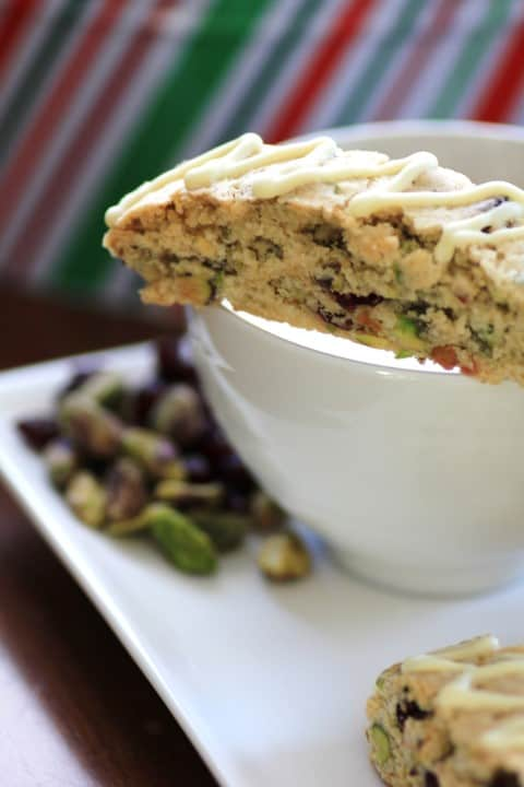 Cranberry Pistachio Biscotti sitting on the rim of a coffee cup