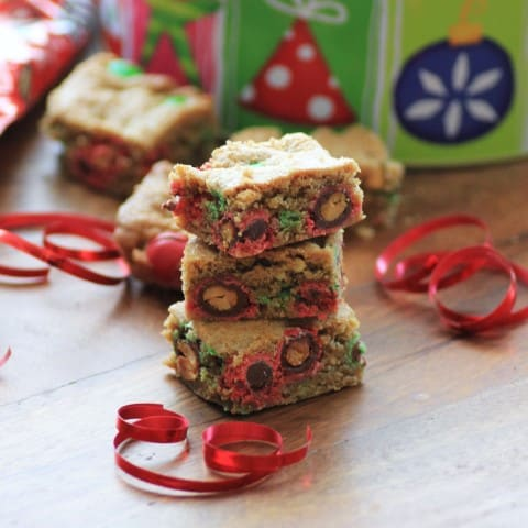 Holiday Cookie Bars squares stacked up on a wooden board