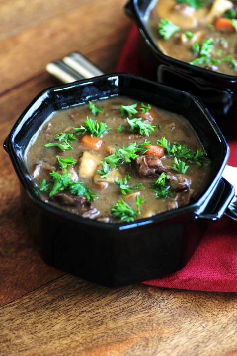 Beef, Wine and Mushroom Soup in a black serving bowl on a wooden table
