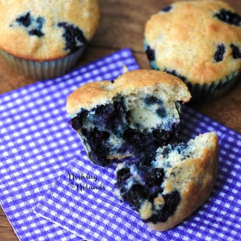Blueberry Muffins, one broken in half on a purple and white checkered napkin