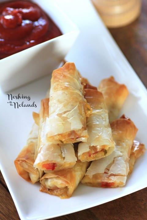 Italian Spring Rolls stacked on a white plate with dipping sauce in a white bowl