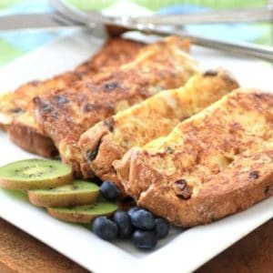 Panettone French toast on a white plate with sliced kiwi and blueberries