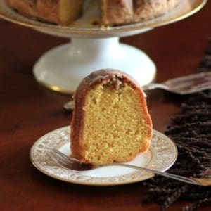 Slice of Rum Pecan bundt on a white and gold china plate with a fork