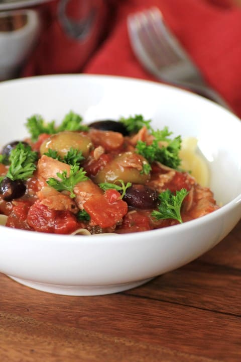 Slow Cooker Chicken Cacciatore in a white bowl with parsley for garnish