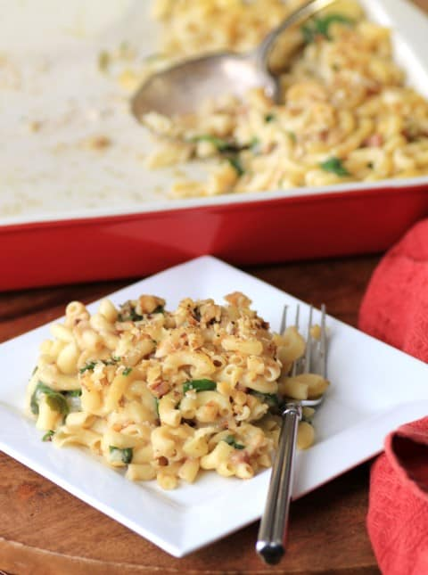 Spinach Prosciutto Macaroni and Cheese on a white plate with a fork