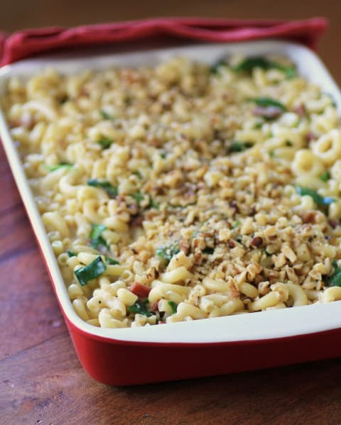 Spinach Prosciutto Macaroni and Cheese in a red and white casserole dish