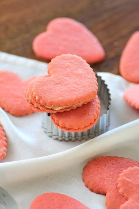 Pink Valentine Heart Cookies on a white table cloth and wooden board