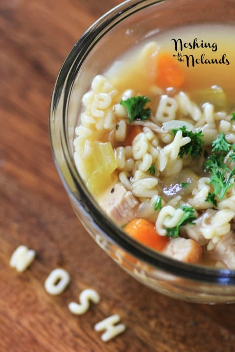 Alphabet Soup in a clear glass bowl with the noodles spelling NOSH on the board in front of the bowl