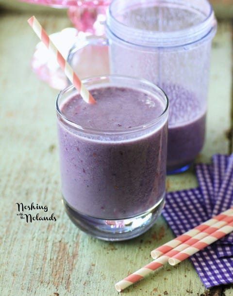 Banana and Blackberry Smoothie in a short glass with a red and white paper straw on a green board