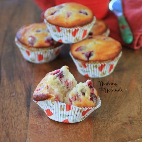 Cranberry Lemon Almond Muffins with one broken in half on a wooden cutting board