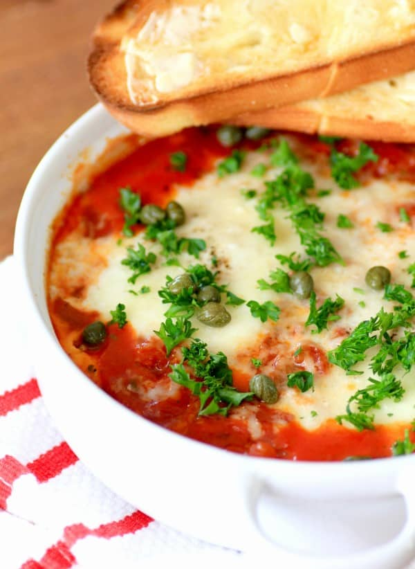 Eggs in Purgatory garnished with parsley and capers with toast in a white bowl