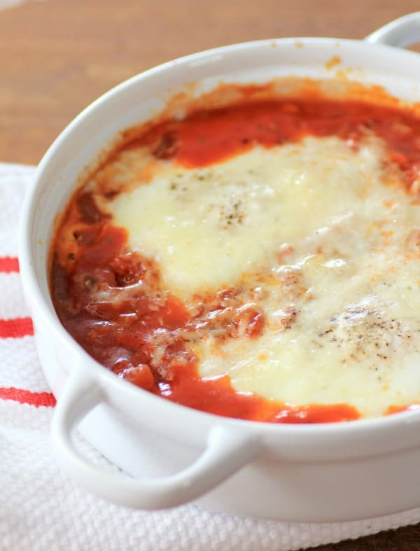 Eggs in Purgatory in a white bowl sitting on a red and white tablecloth