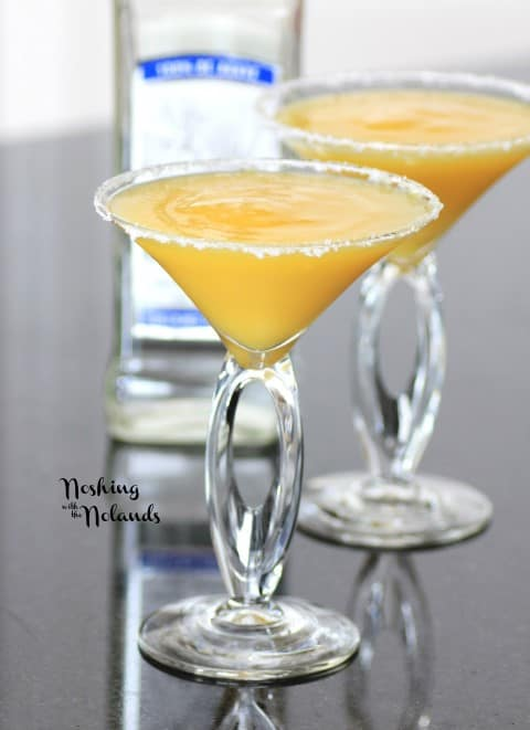 2 glasses filled with Frozen Mango Margarita with salted rims