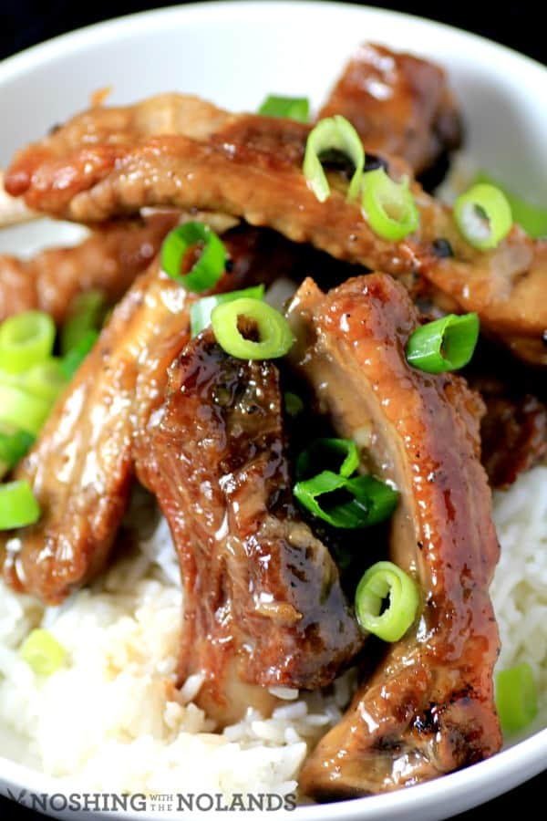 Sweet and Sour Ribs served over white rice garnished with chopped green onions