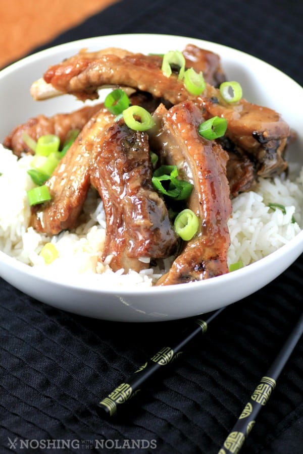 Sweet and Sour Ribs served in a white bowl over white rice garnished with chopped green onions