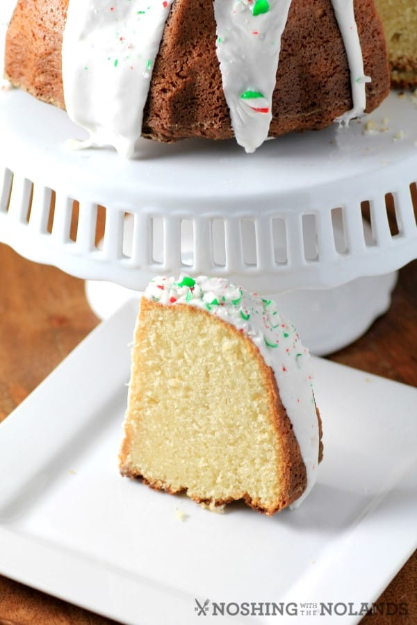 White Hot Chocolate Peppermint Bundt slice on a white plate with the reat of the cake on a white cake stand