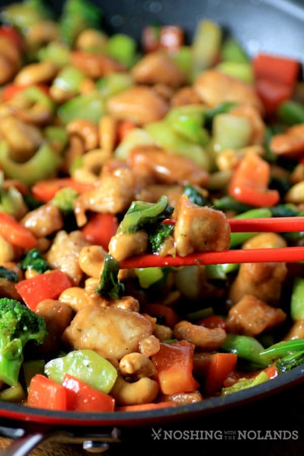 Asian Skillet Stir Fry in a red skillet with chop sticks picking up a bite