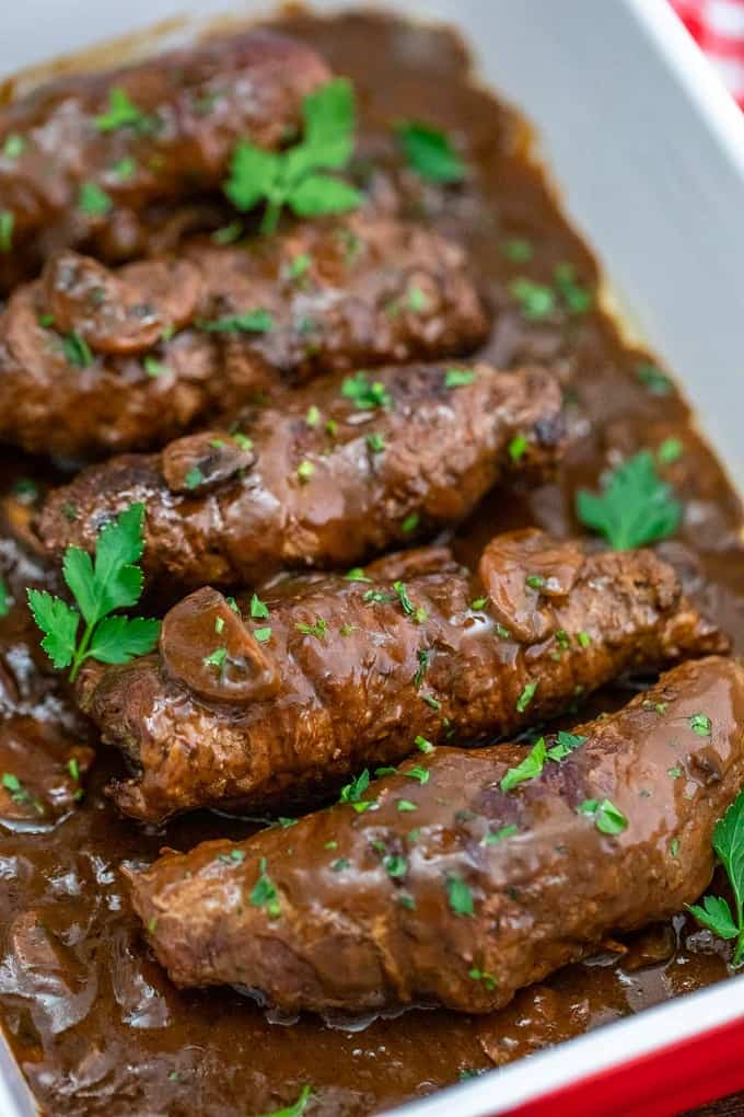 Beef rouladen in a red and white casserole dish with mushroom gravy and cilantro