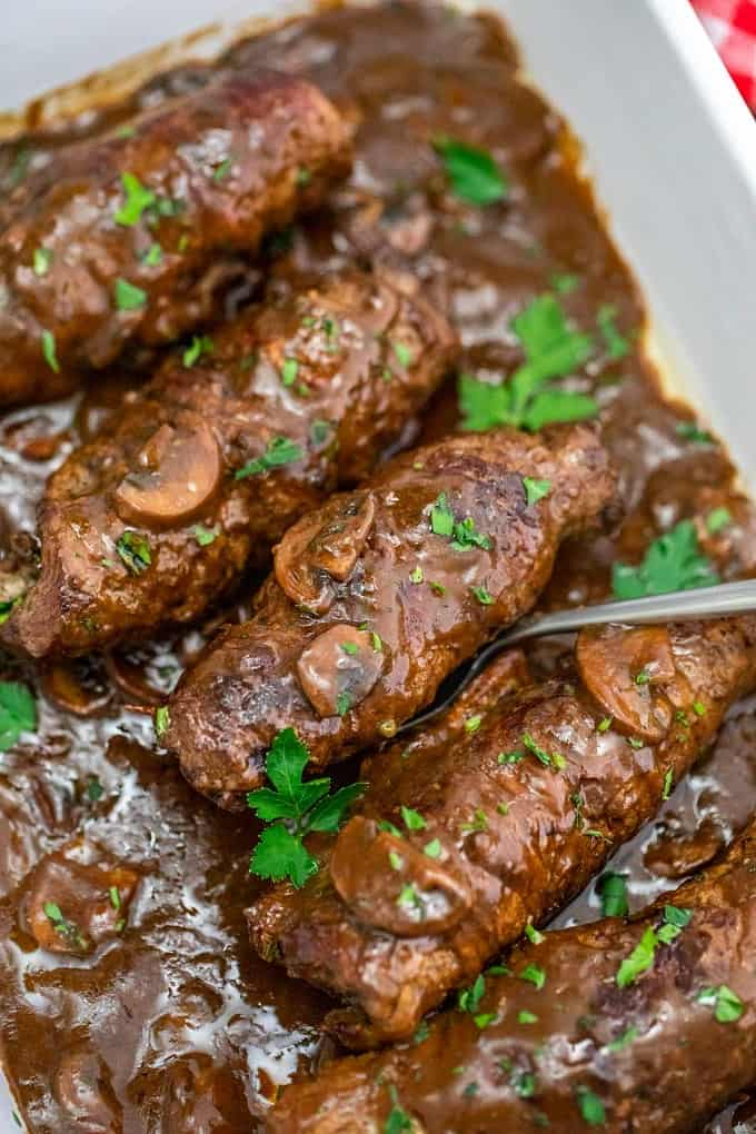 Beef Rouladen in a casserole dish with a silver serving spoon