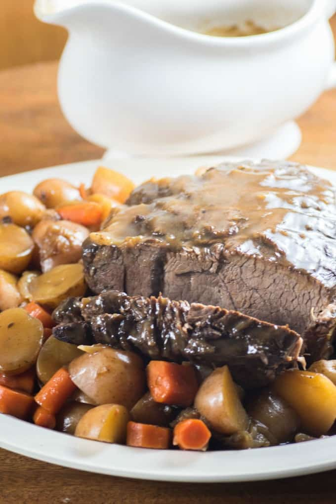 Cooked pressure cooker roast beef on a platter with gravy boat