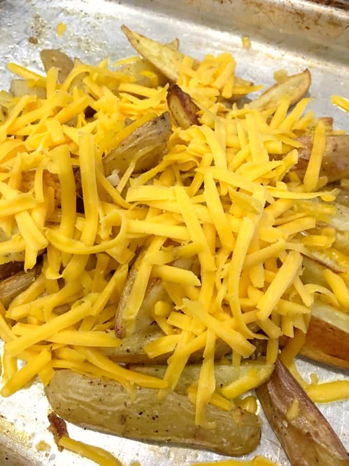 Grated cheese on top of home fries on a baking sheet