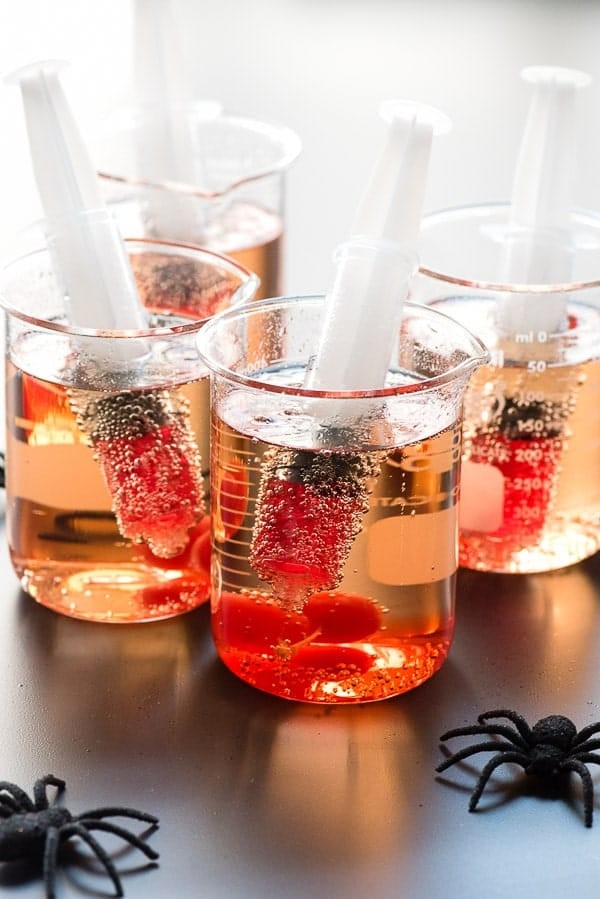 Shirley Temples served in beakers with red fluid syringes