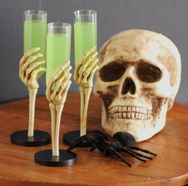 Green cocktail in skeleton glasses with a skeleton head and spider