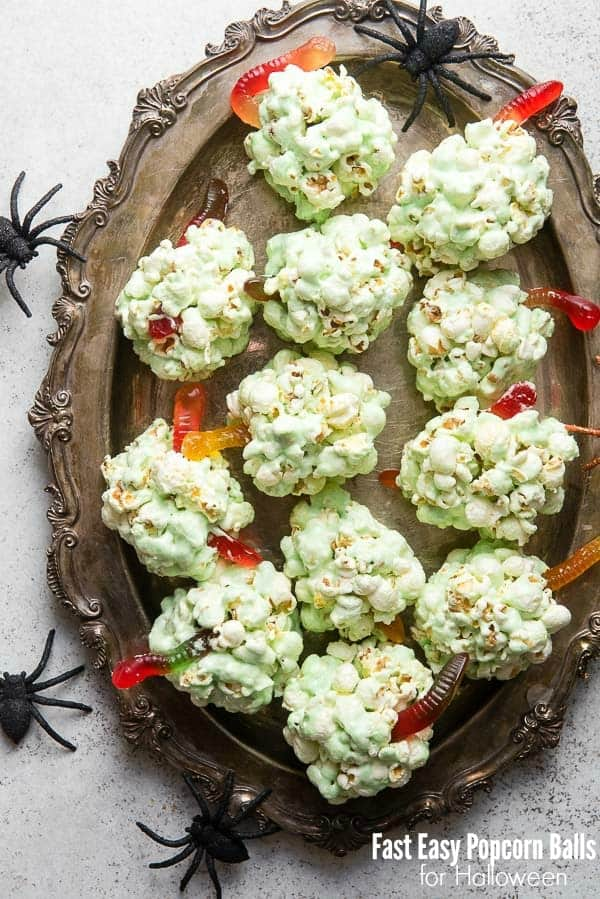 Green popcorn balls with gummy worms coming out on a platter with spiders around the outside