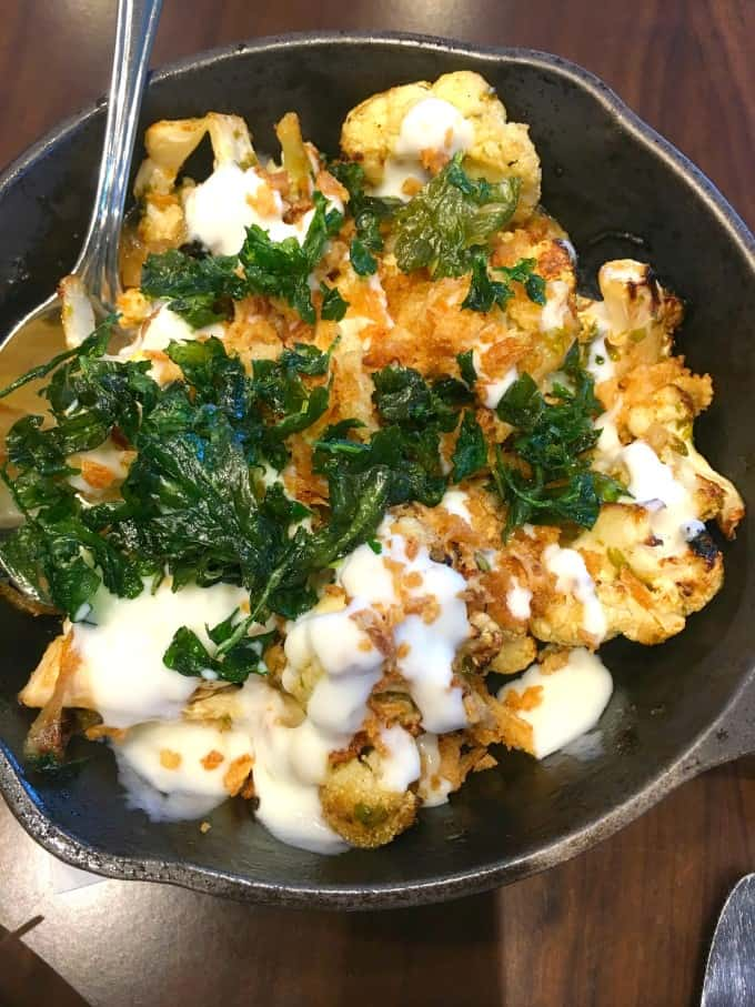 Cauliflower is served up with lemon yogurt, cumin vinaigrette and caramelized onions in a black bowl