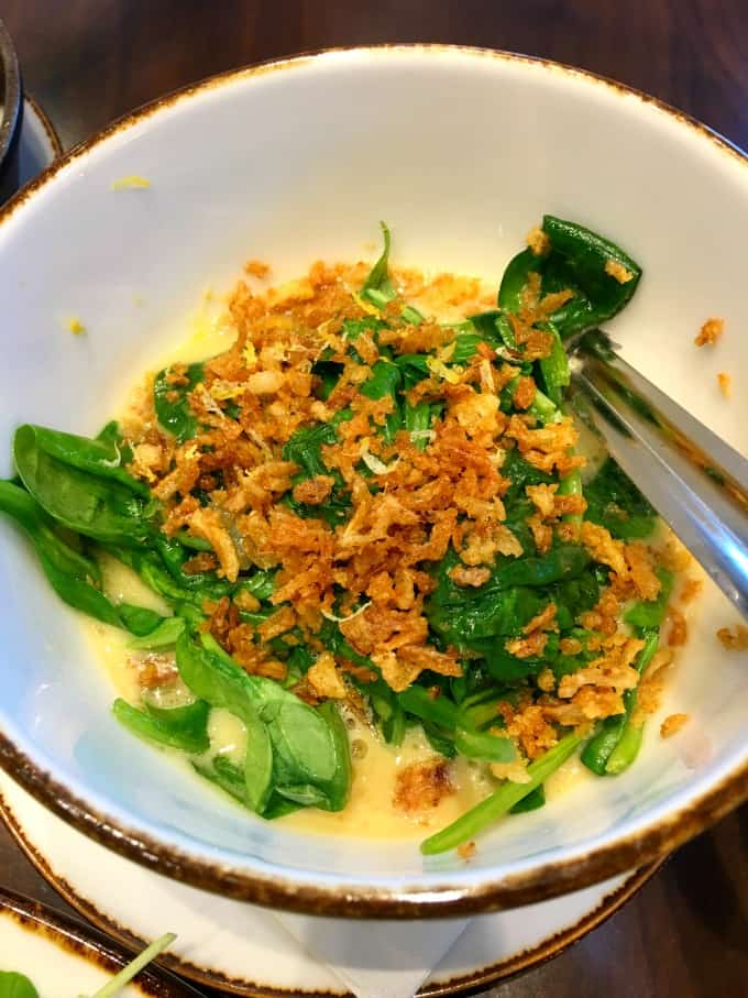 Spinach with crispy shallots in a white bowl
