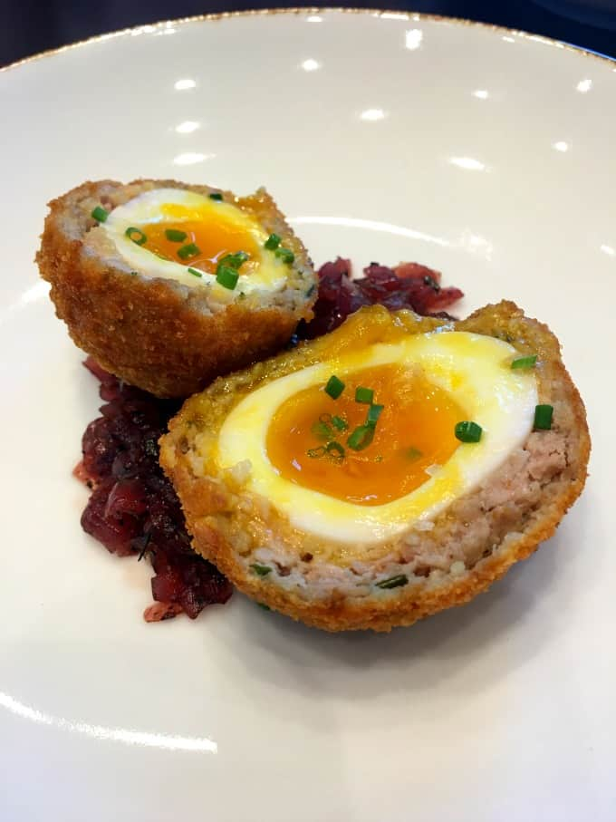 Scotch Egg on a white plate with truffled red onion jam