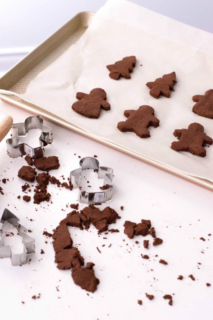 Cutout ornaments on a parchment lined cookie sheet with crumbs and cookie cutters